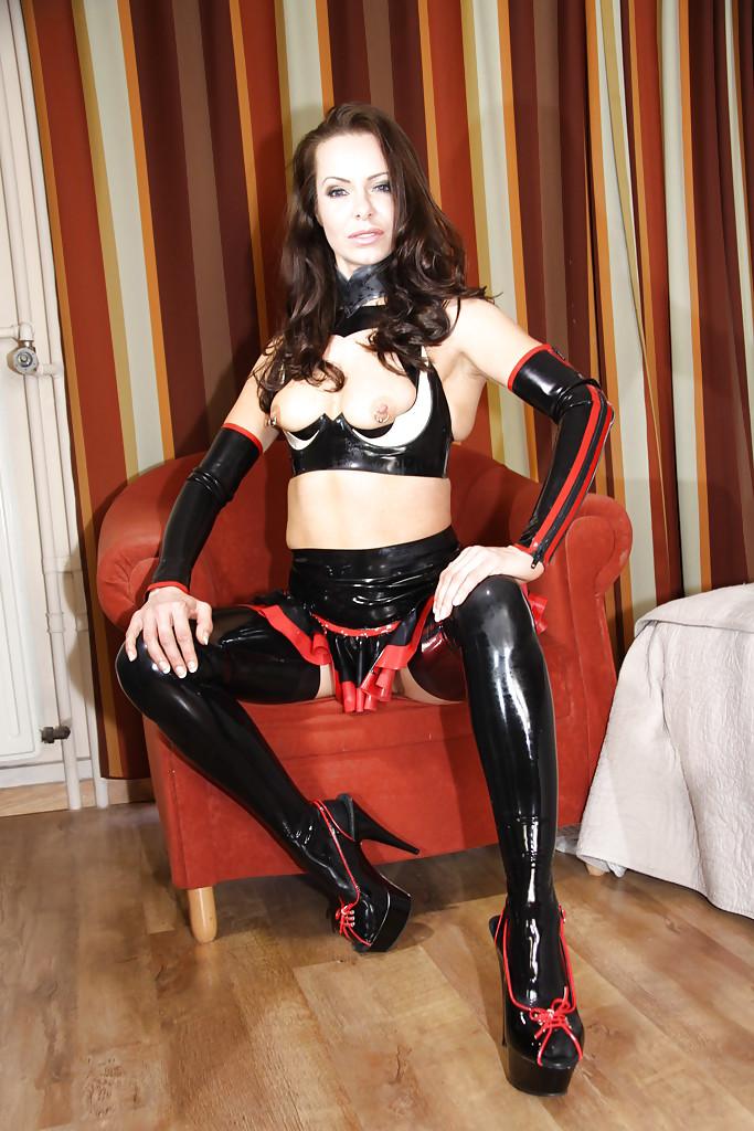 Зрелая тёлка в латексном наряде демонстрирует тело на красном кресле секс фото и порно фото